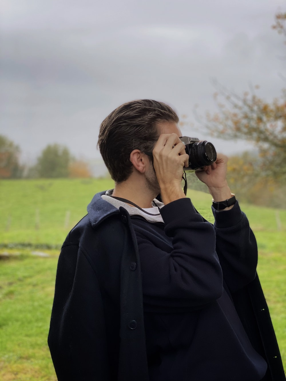 man in black jacket using binoculars