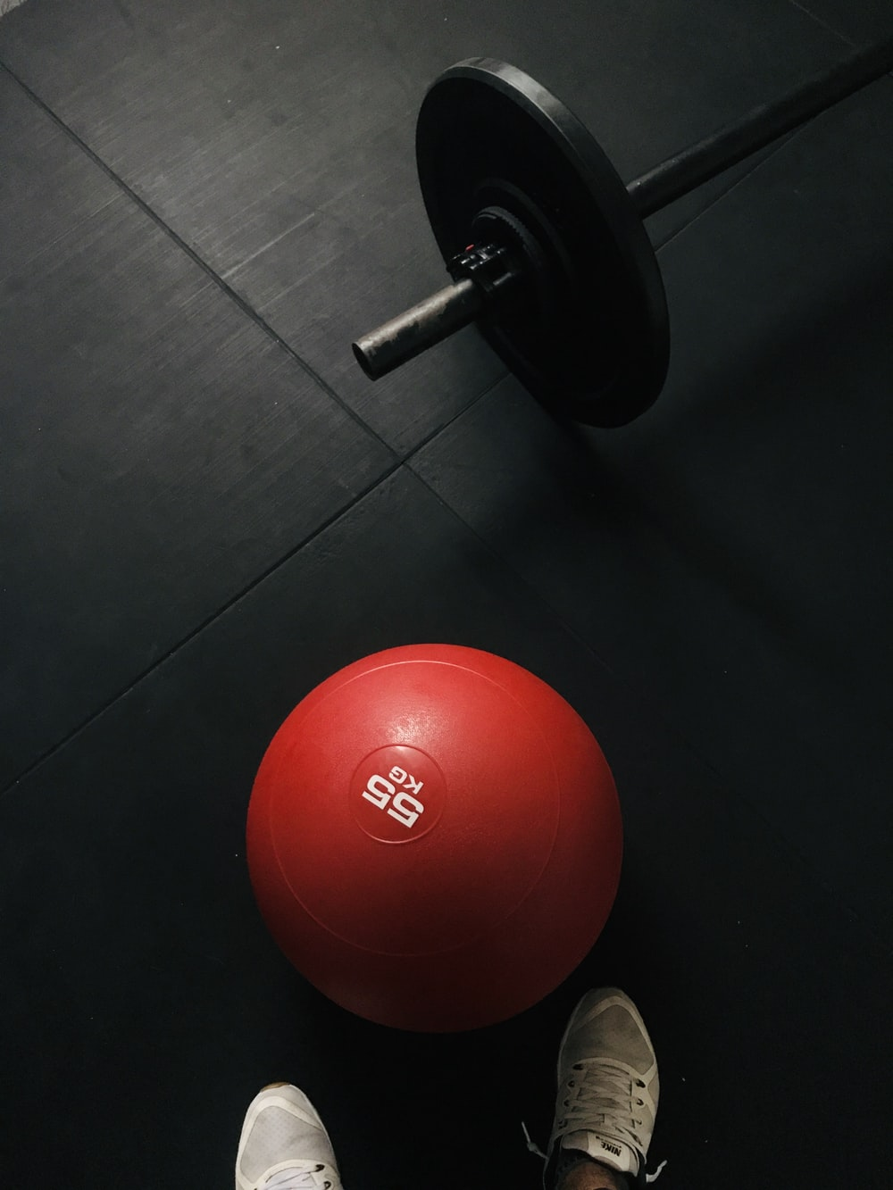 red and black dumbbell on black floor