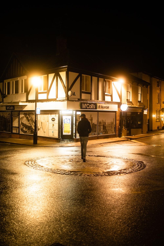 man in black jacket standing on pedestrian lane during night time