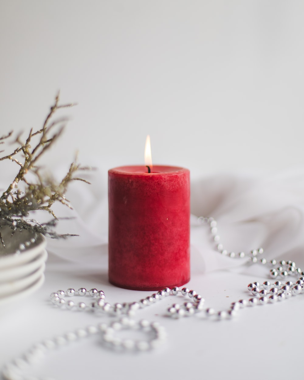 red pillar candle on white table cloth