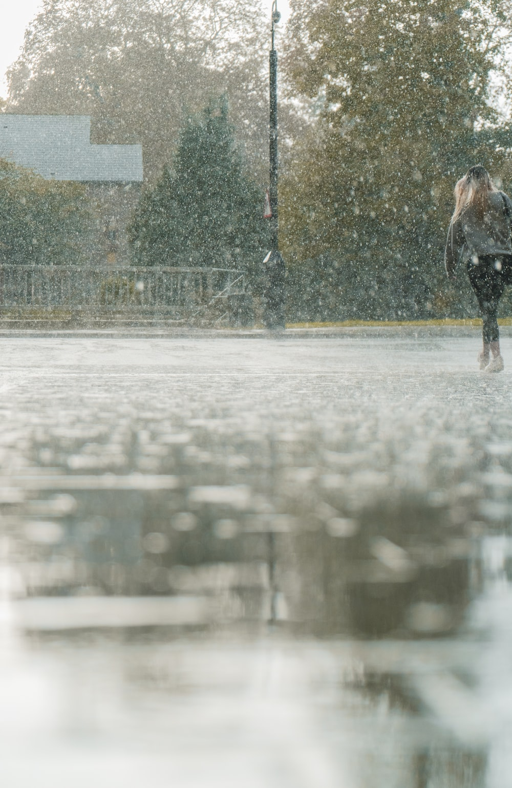 person in black jacket walking on wet road during daytime