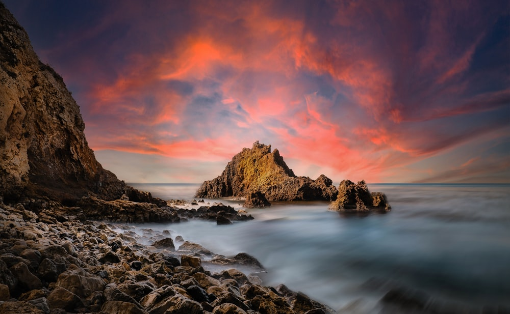 rocky shore with rocks under orange and blue sky