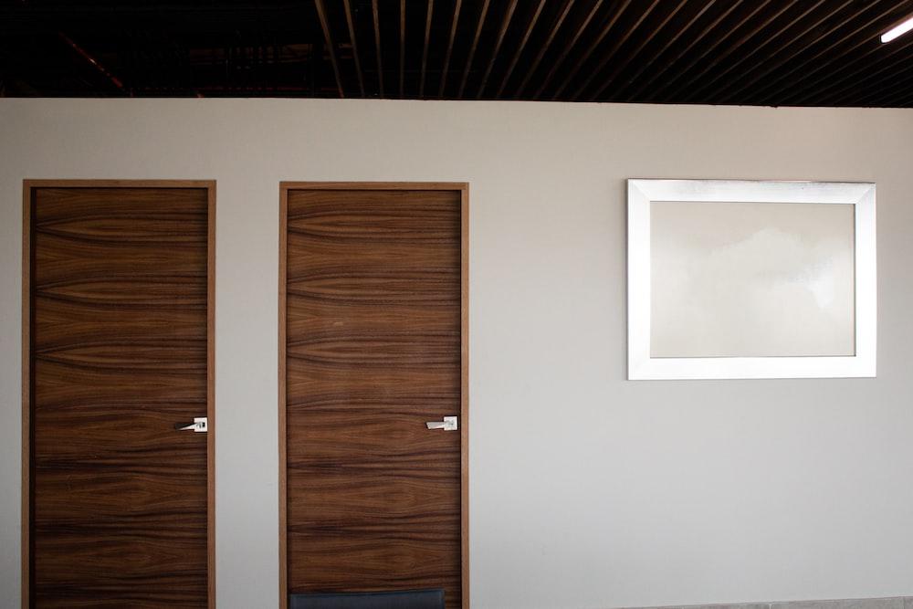 brown wooden door beside white wall