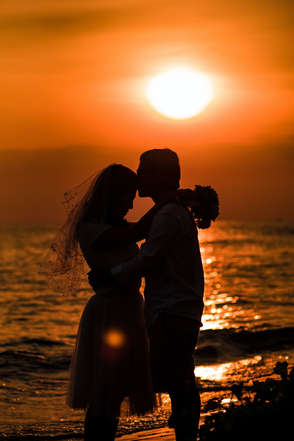 man and woman kissing on beach during sunset