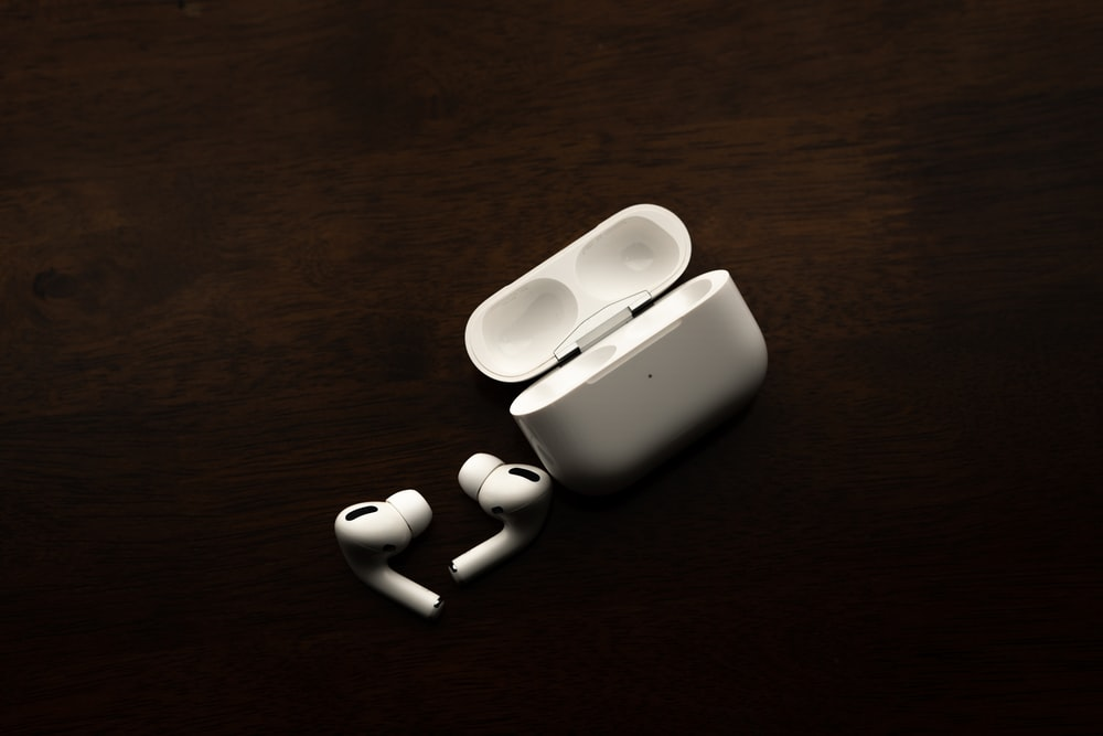 white apple earpods on brown wooden table