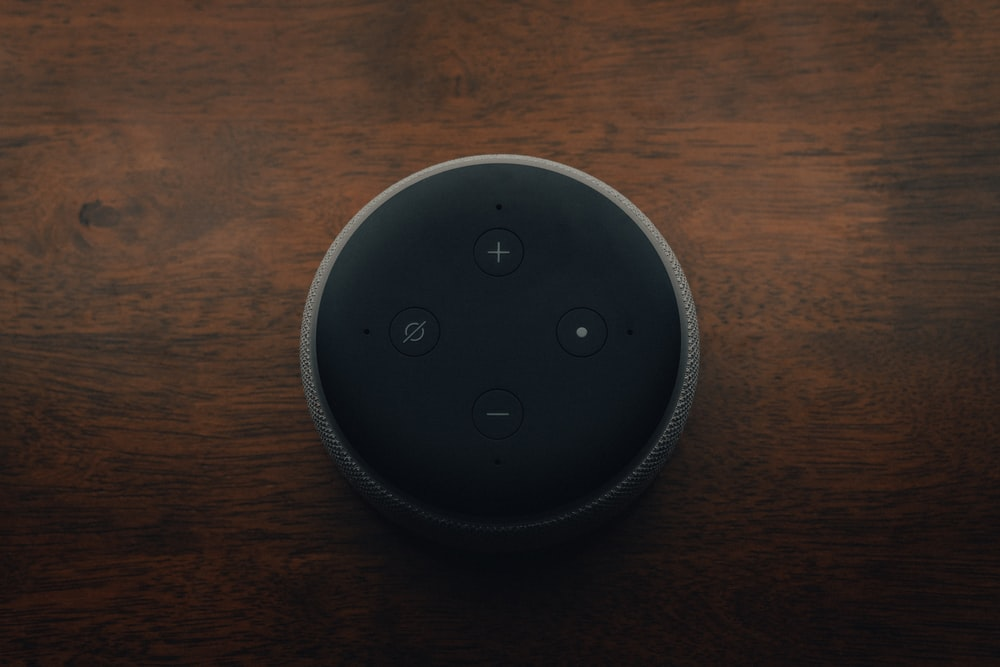 black amazon echo dot on brown wooden table