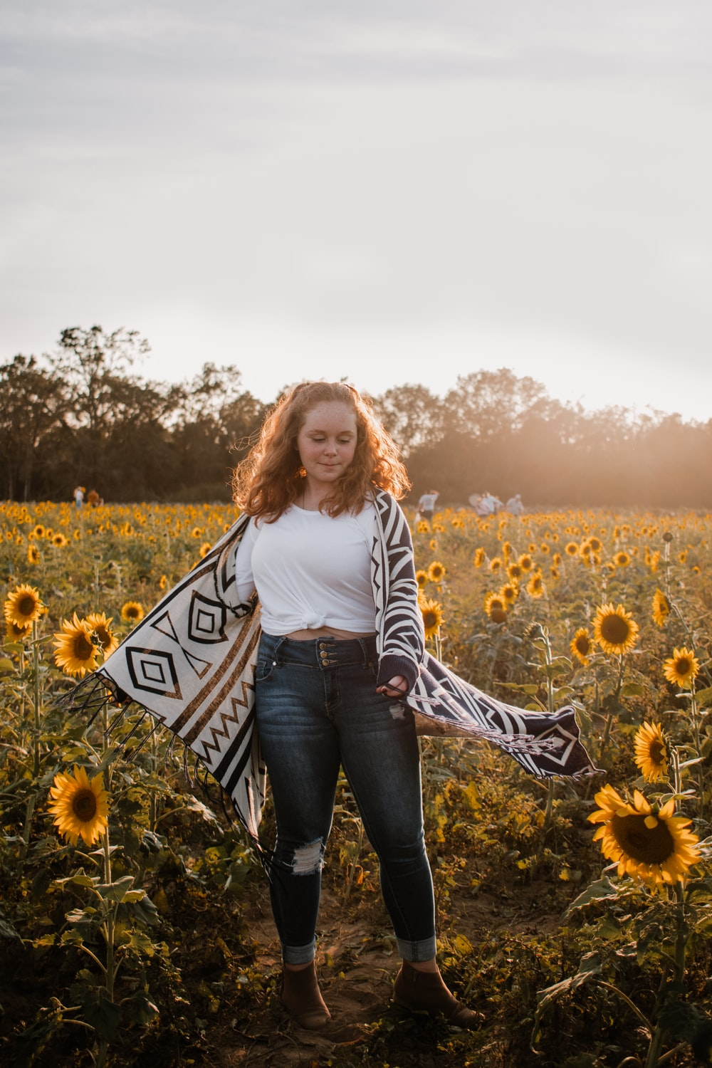 woman in white long sleeve shirt standing on yellow flower field during daytime