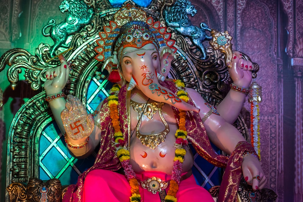 hindu deity statue with green and blue dragon head