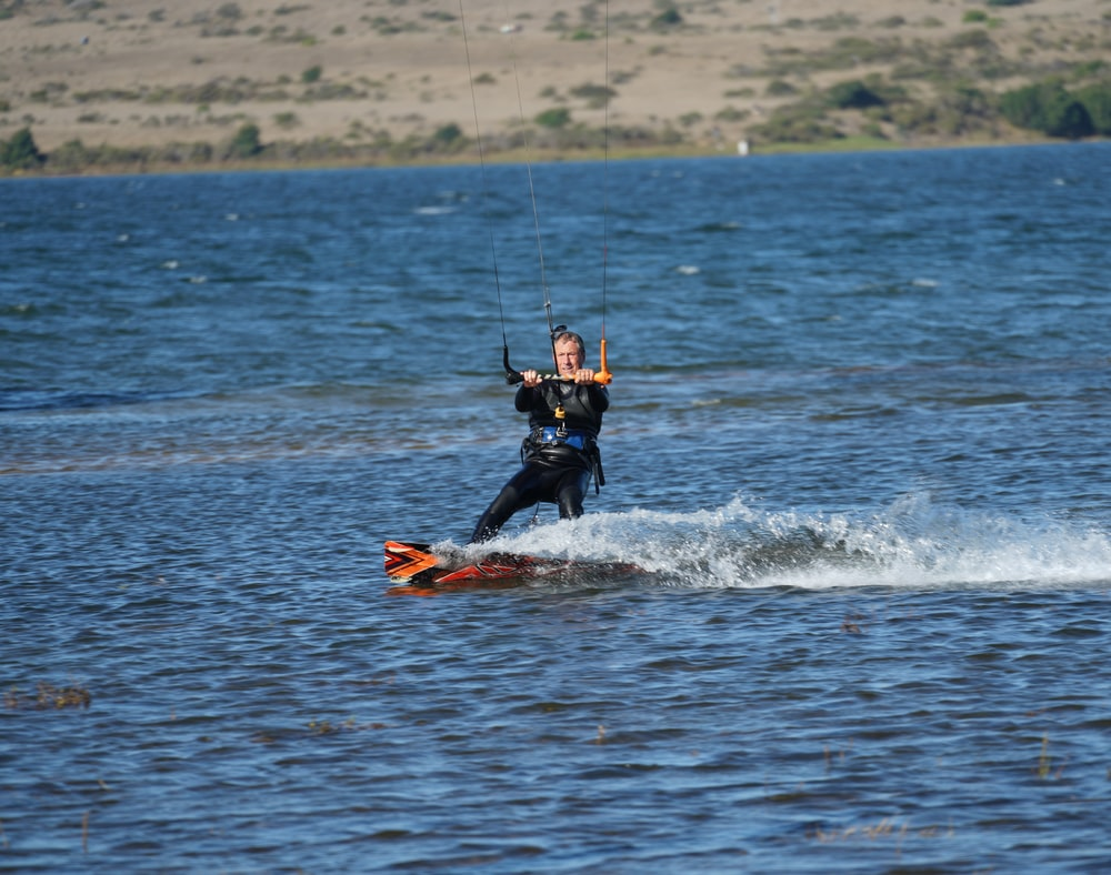 man in orange and black wet suit surfing on sea during daytime