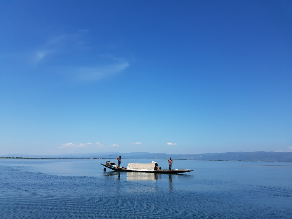 people on boat on sea under blue sky during daytime