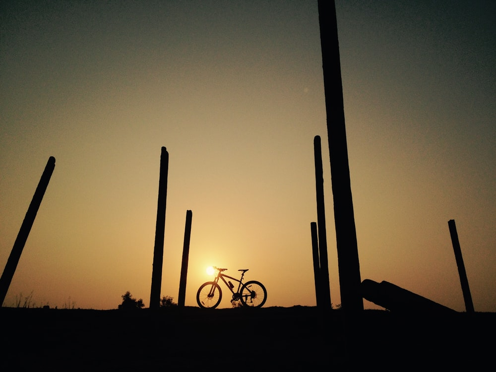silhouette of a man riding bicycle during sunset