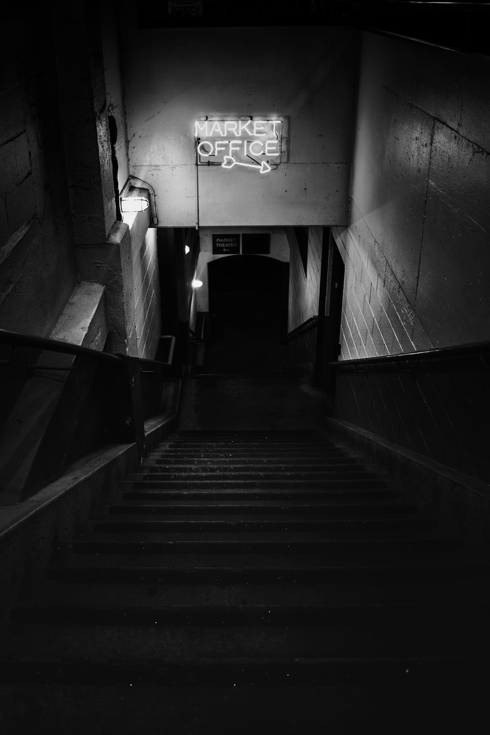 grayscale photo of staircase in tunnel