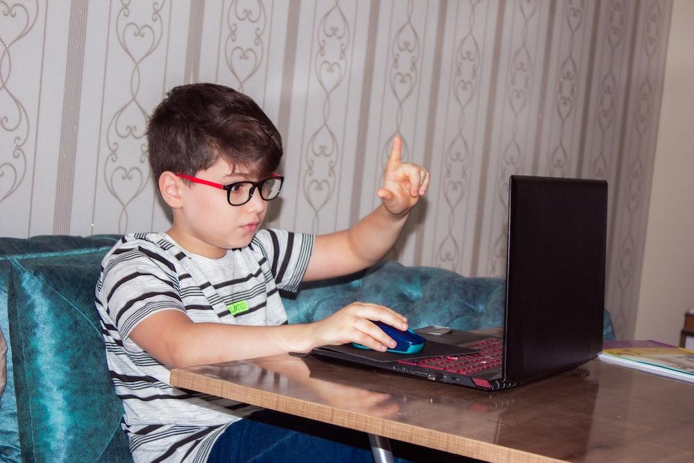 man in black and white stripe shirt using black laptop computer