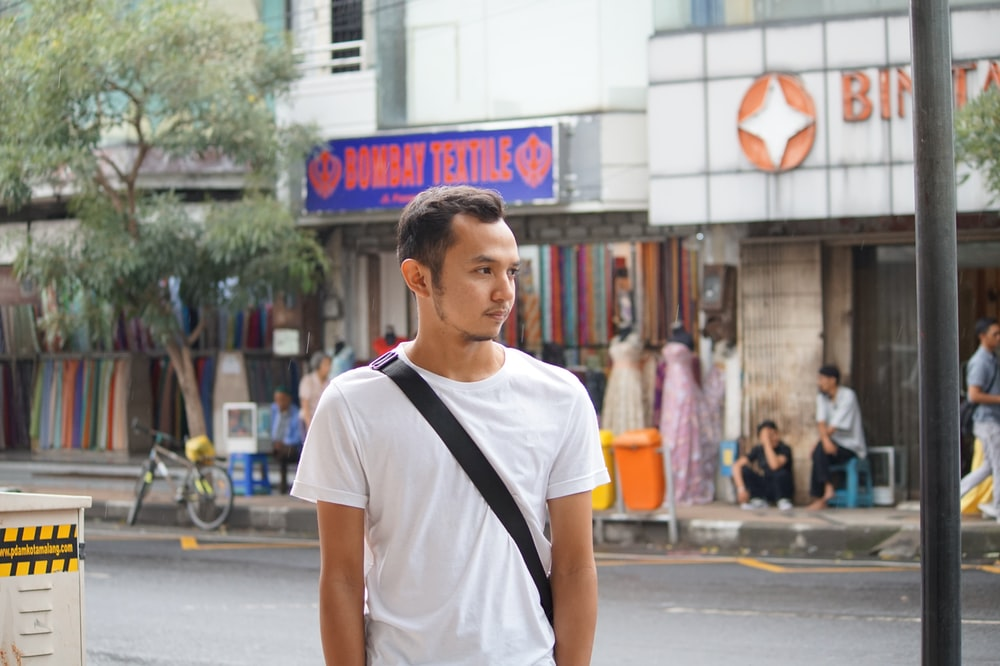 man in white crew neck t-shirt standing on street during daytime