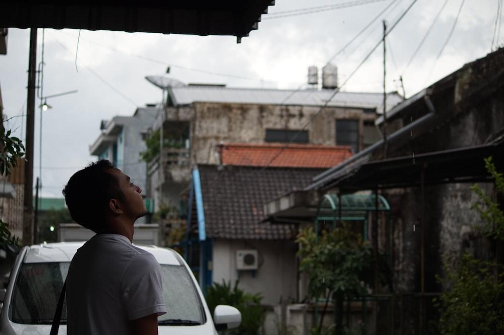 man in white shirt standing near white car during daytime
