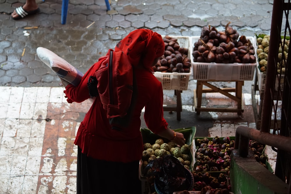 woman in red hoodie standing in front of fruit stand