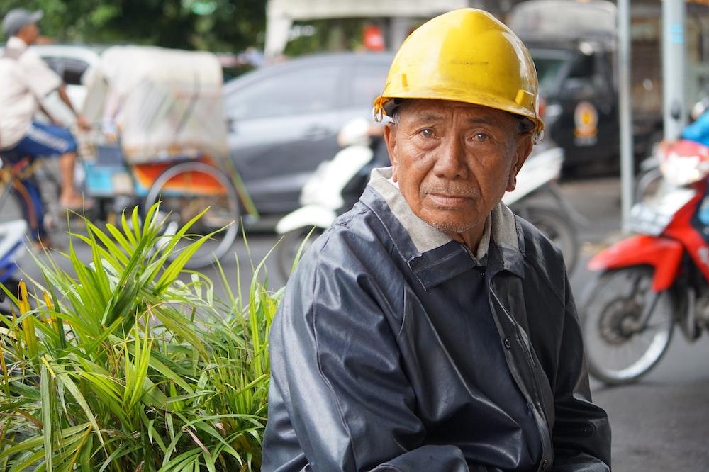man in black jacket wearing yellow hard hat