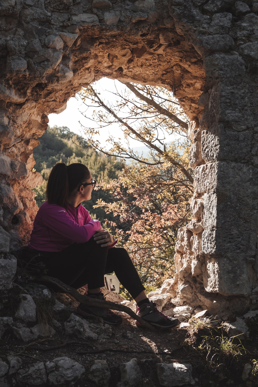 woman in purple long sleeve shirt sitting on rock during daytime