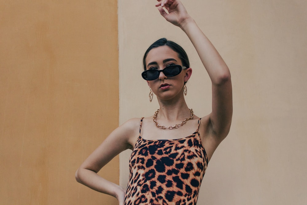 woman in brown and white leopard print tank top wearing black sunglasses