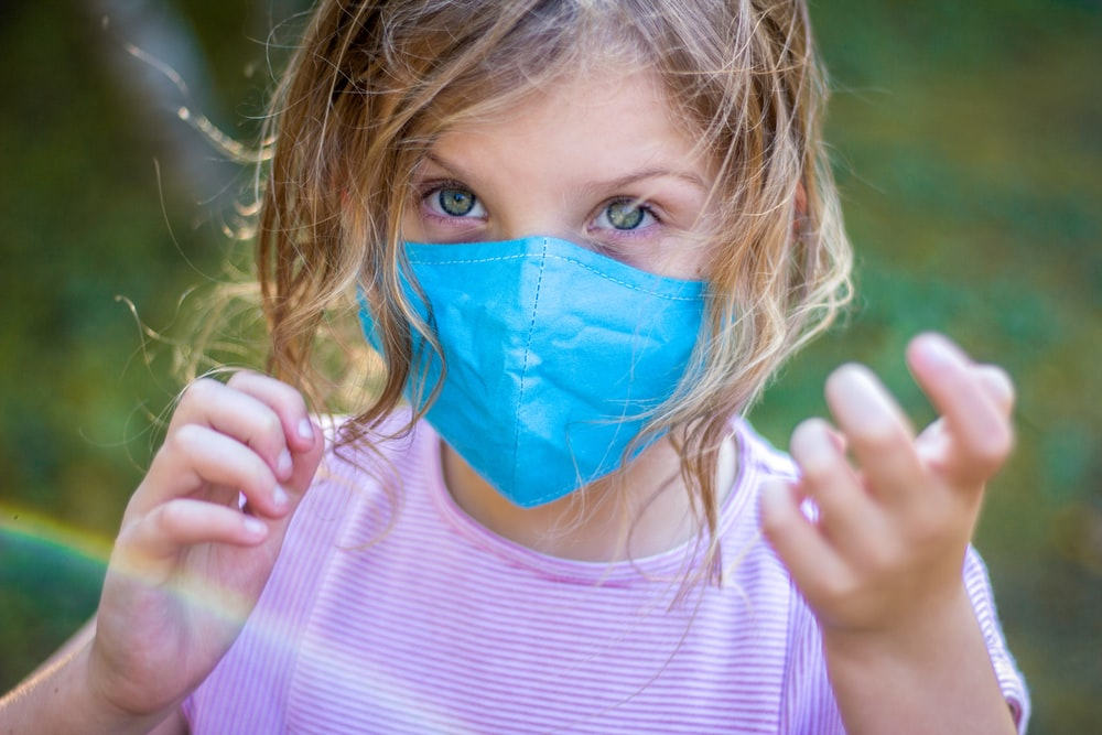 girl in pink crew neck shirt with blue face mask