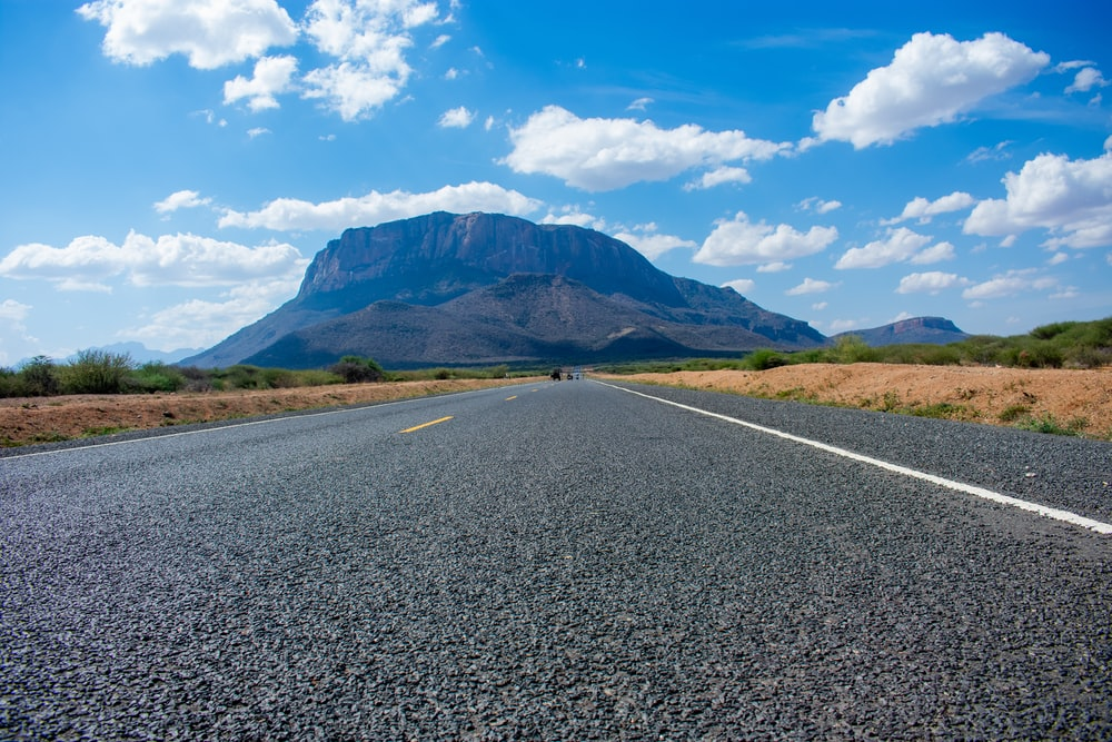 gray asphalt road near green mountains under blue sky during daytime