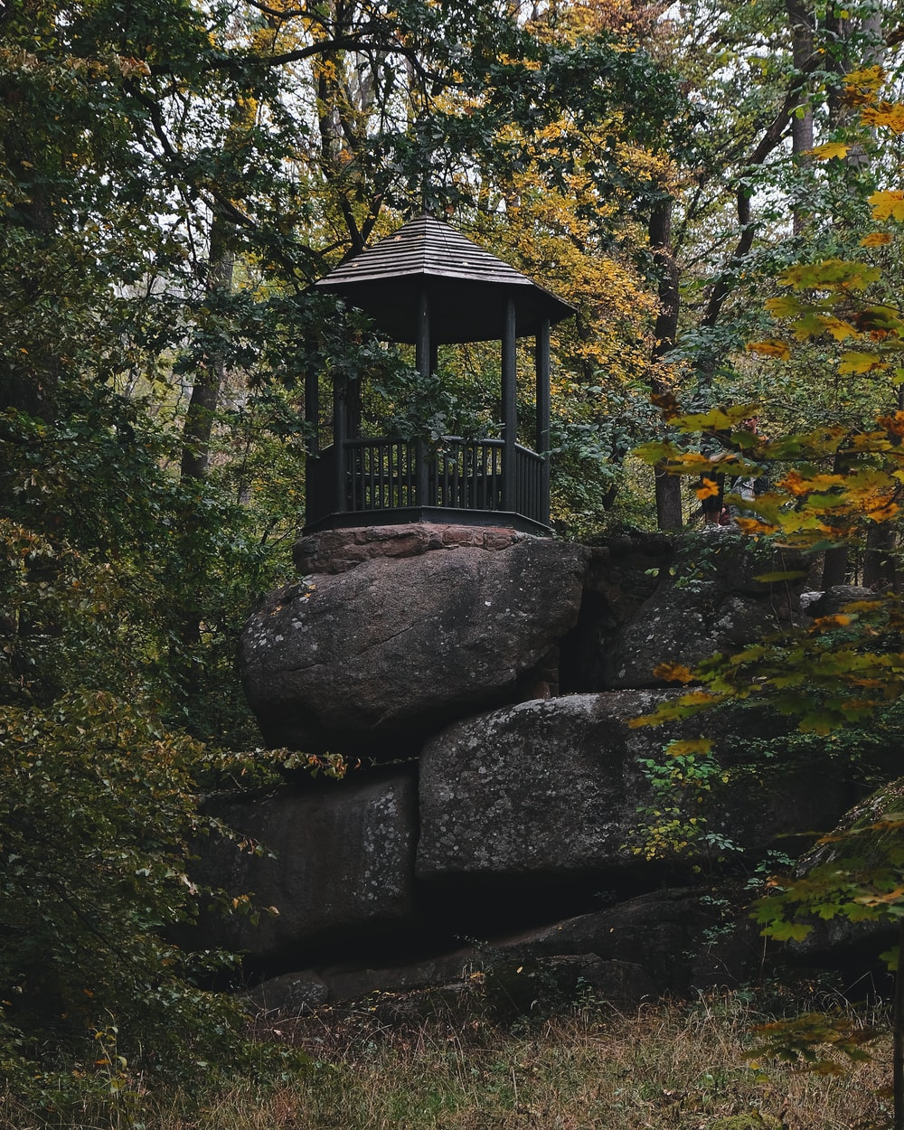 brown wooden gazebo on gray rock formation surrounded by green trees during daytime