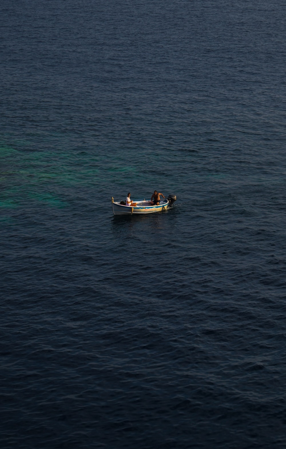 2 people riding on boat on sea during daytime