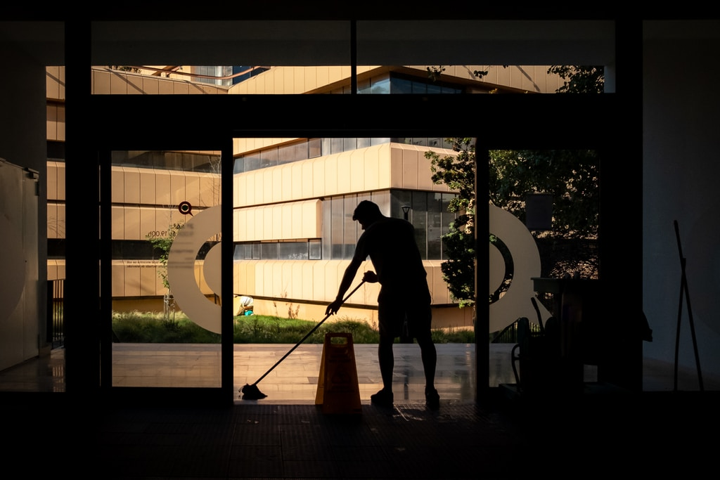 Commercial Cleaning Man cleans floor at an entrance door.