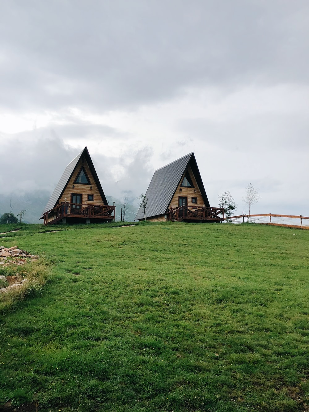 brown wooden house on green grass field under white cloudy sky during daytime