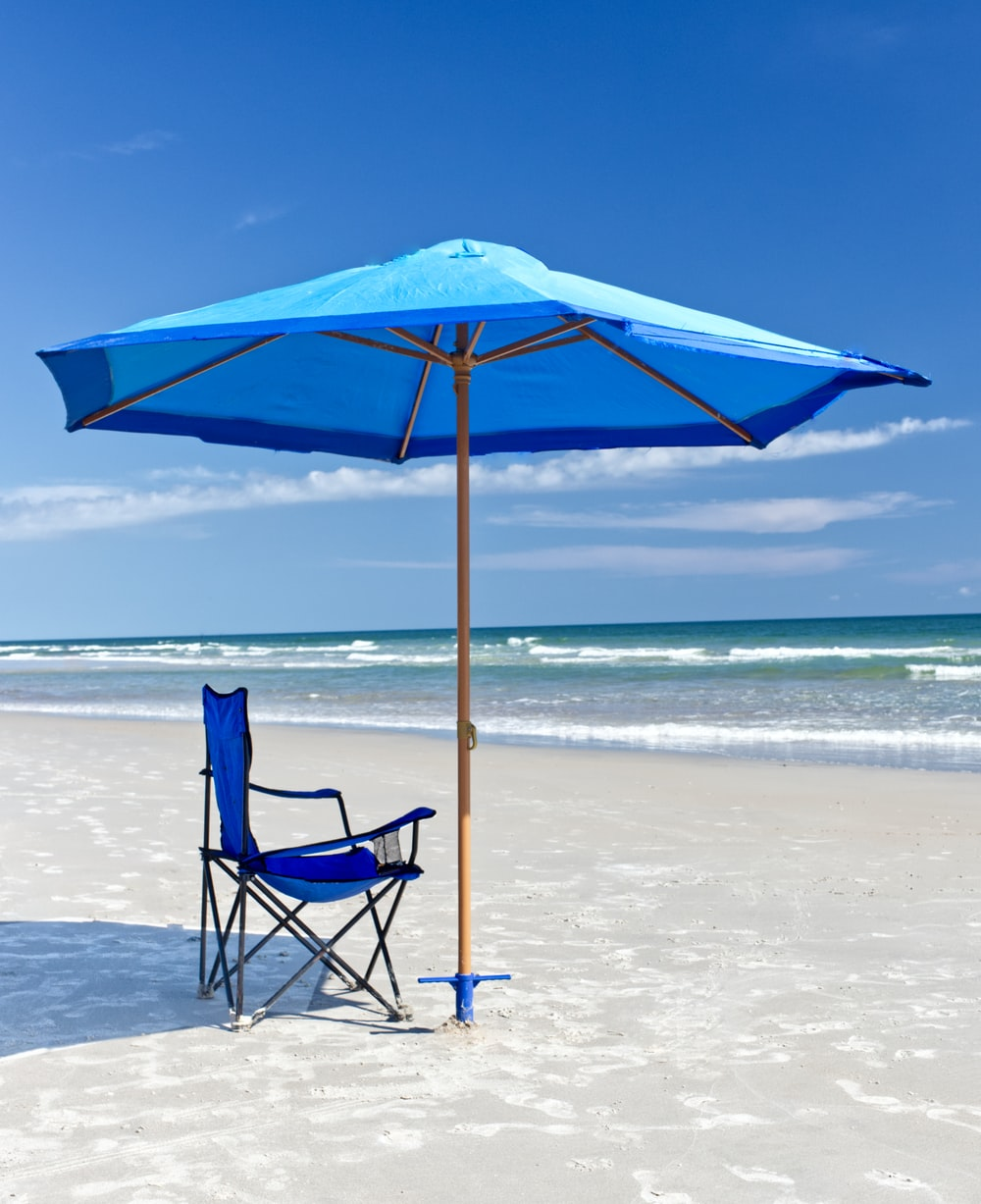 blue and black folding chair on beach during daytime