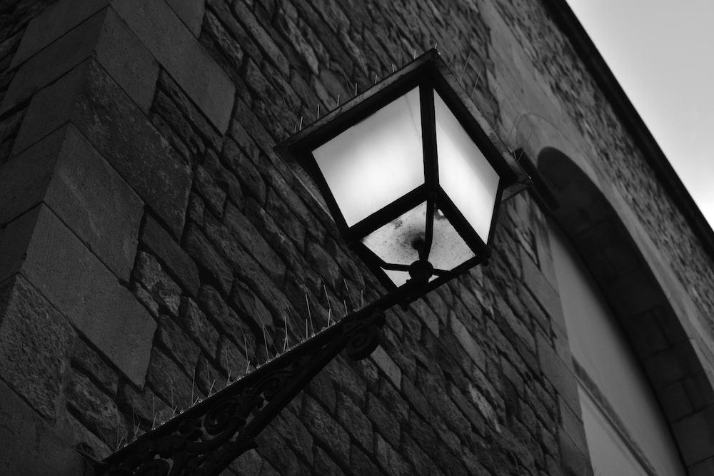black framed wall lamp turned on during daytime
