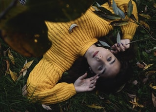 woman in yellow knit sweater lying on green grass