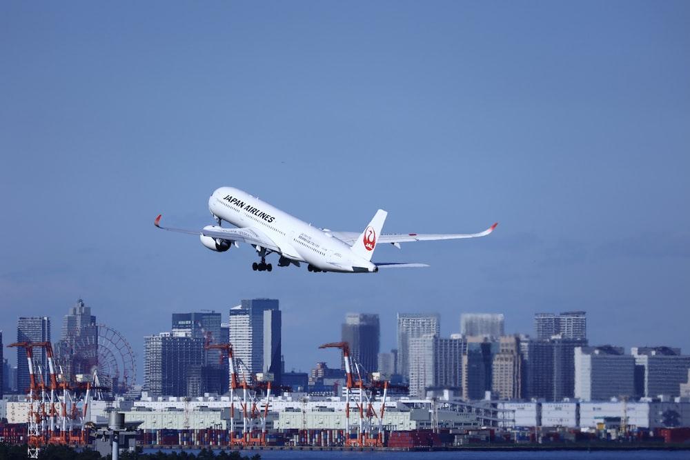 white passenger plane flying over city buildings during daytime