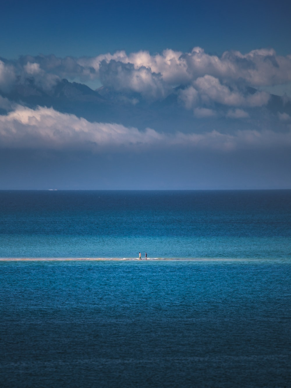 blue sea under white clouds and blue sky during daytime