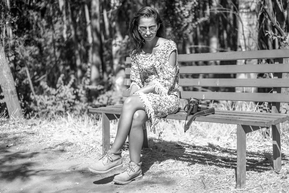 woman in floral dress sitting on bench
