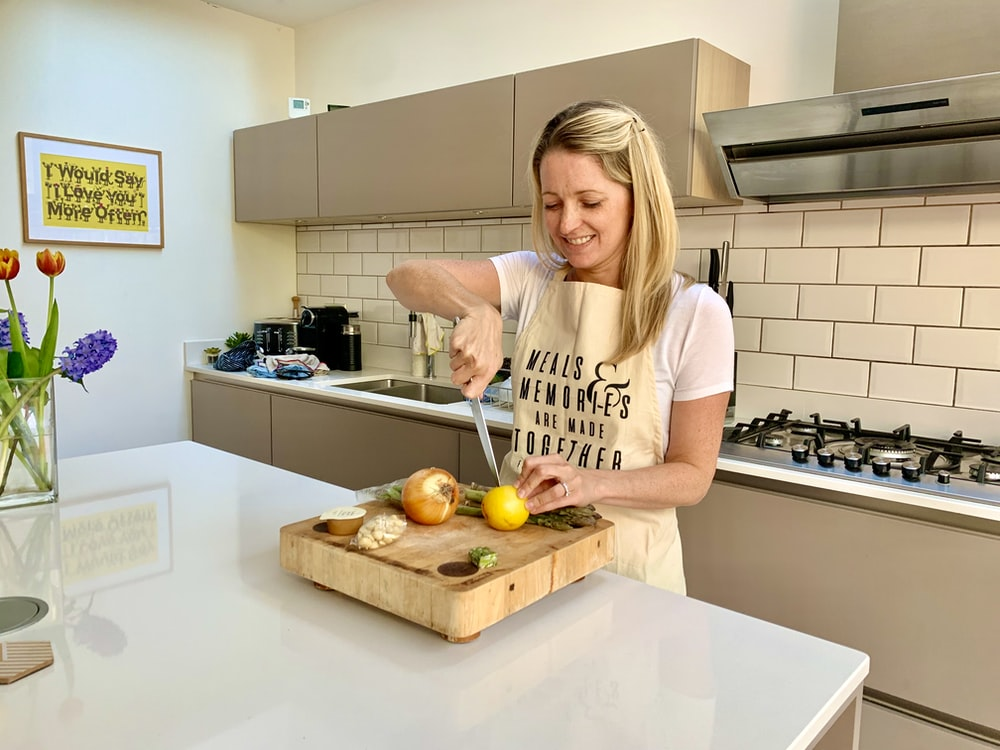 woman in white and black crew neck t-shirt standing in kitchen