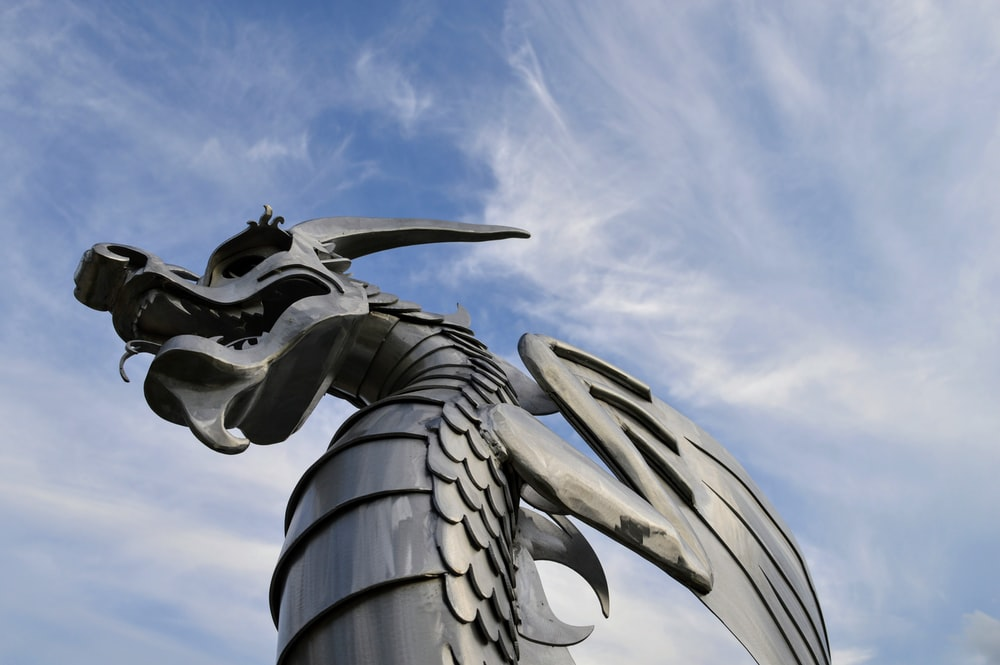 gray dragon statue under blue sky during daytime