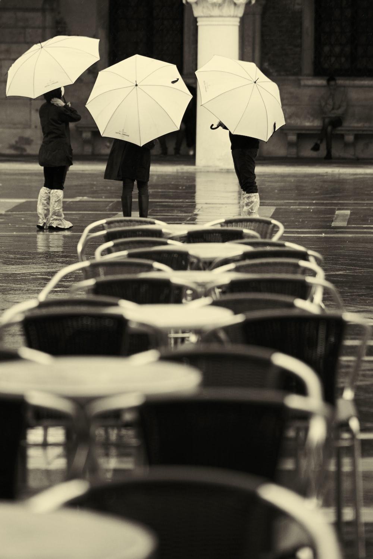 person in black jacket holding umbrella walking on sidewalk during daytime