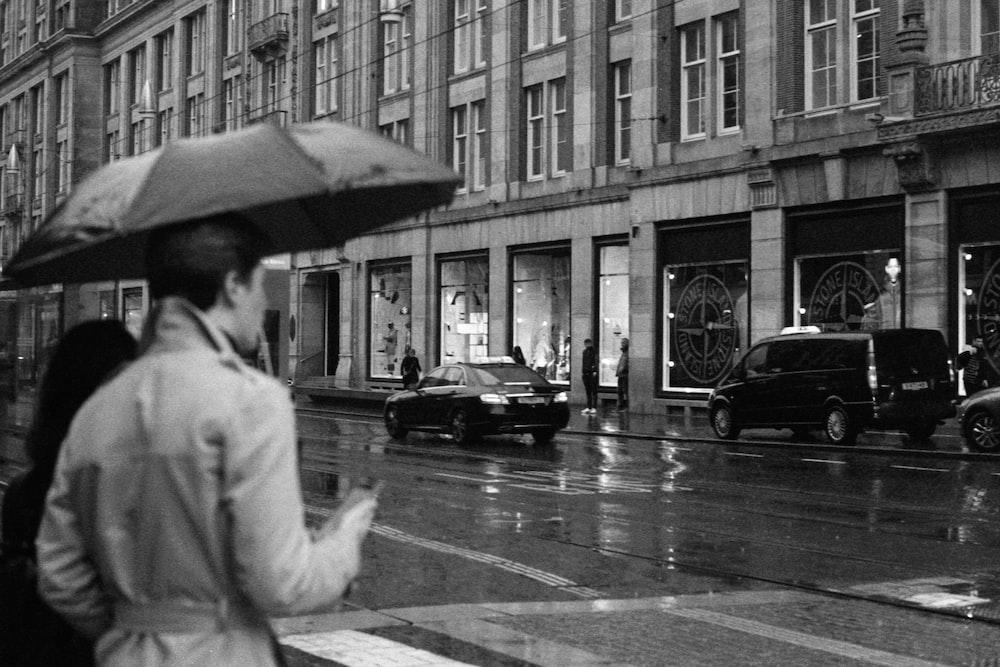 grayscale photo of man in white robe holding umbrella walking on pedestrian lane