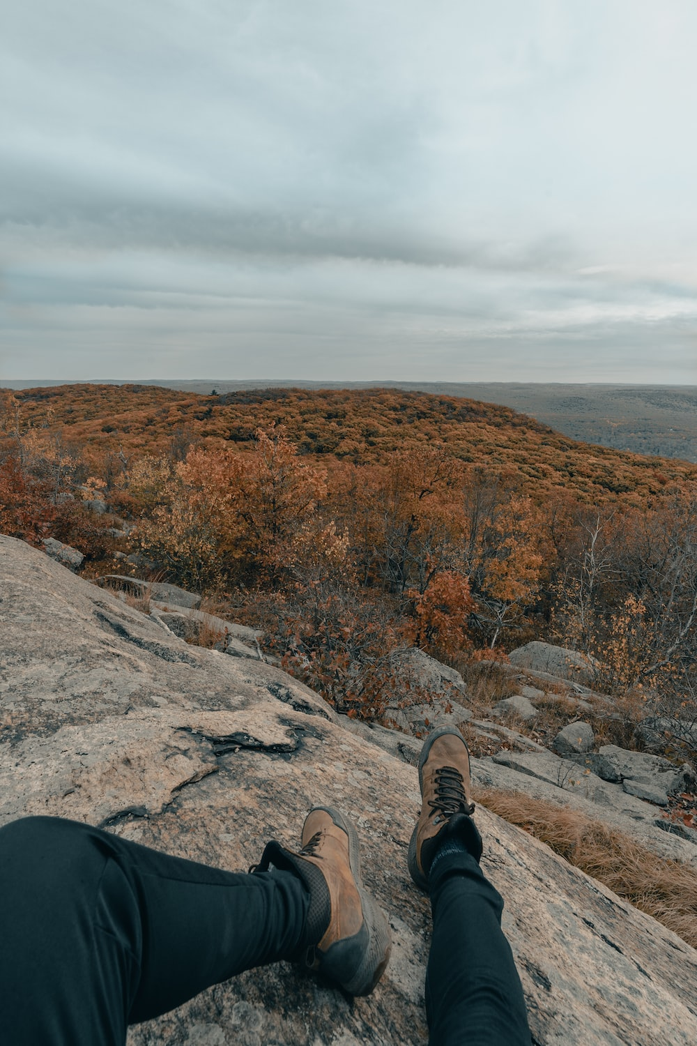 person in black pants and brown hiking shoes sitting on rock during daytime