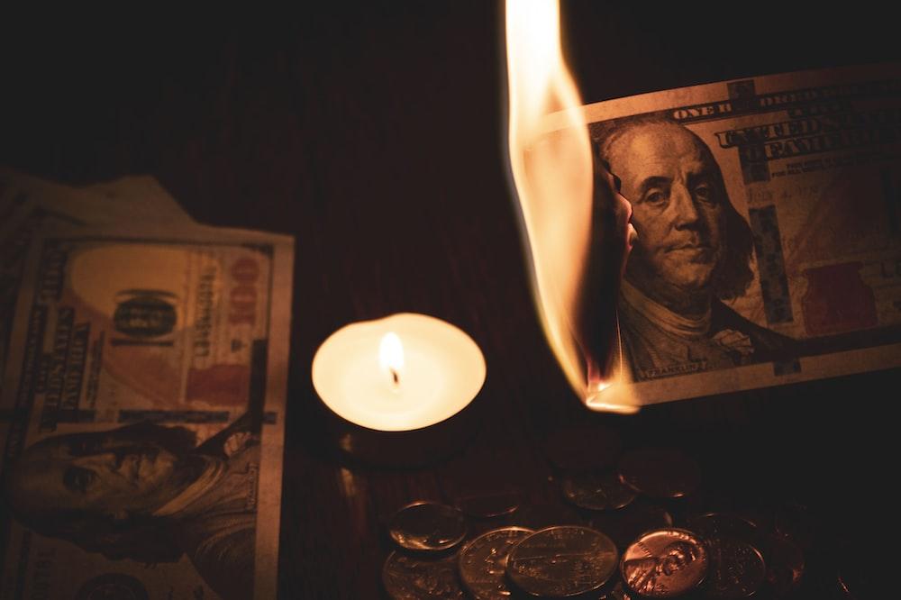 white pillar candle beside 100 us dollar bill