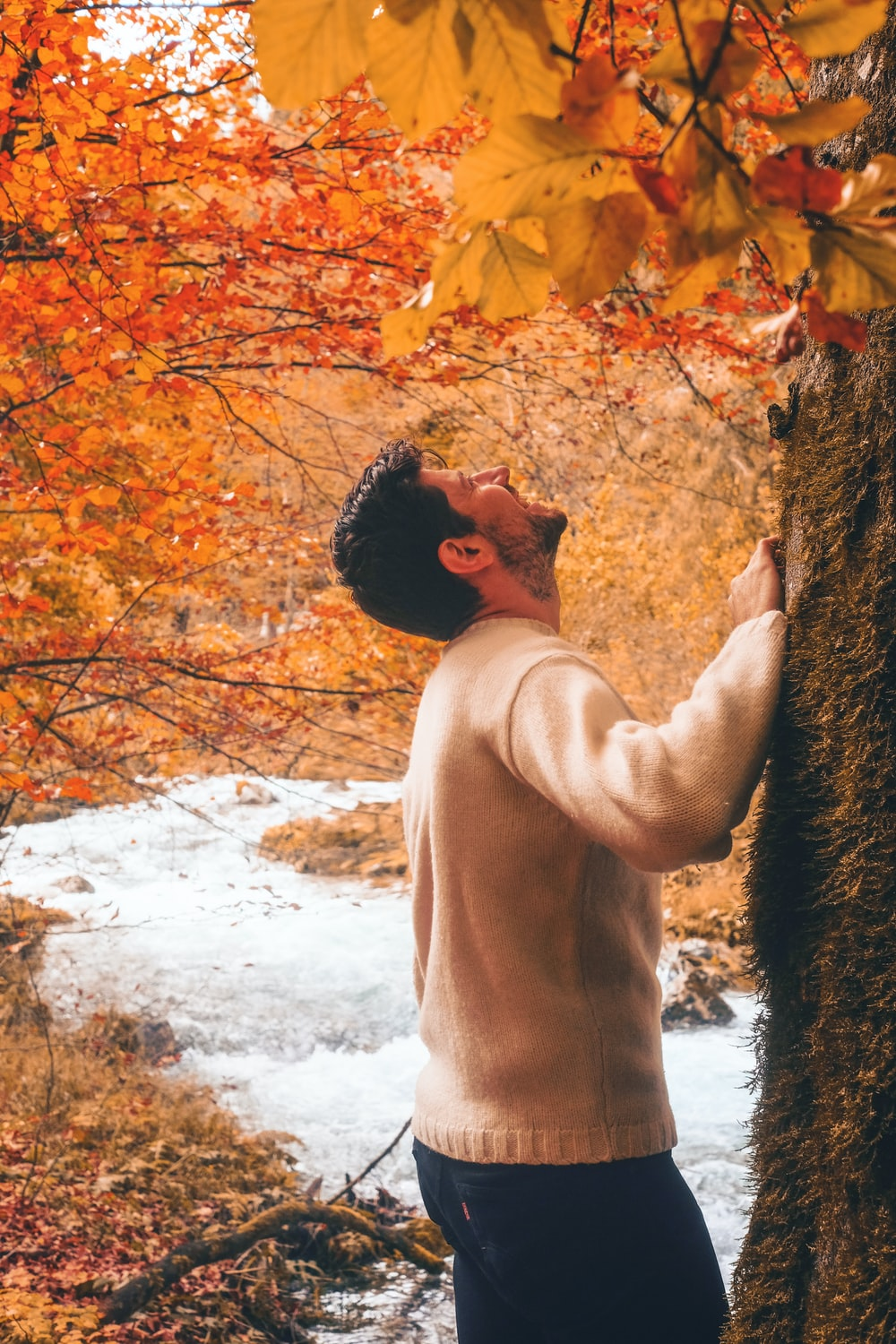 man in white sweater leaning on brown tree trunk during daytime