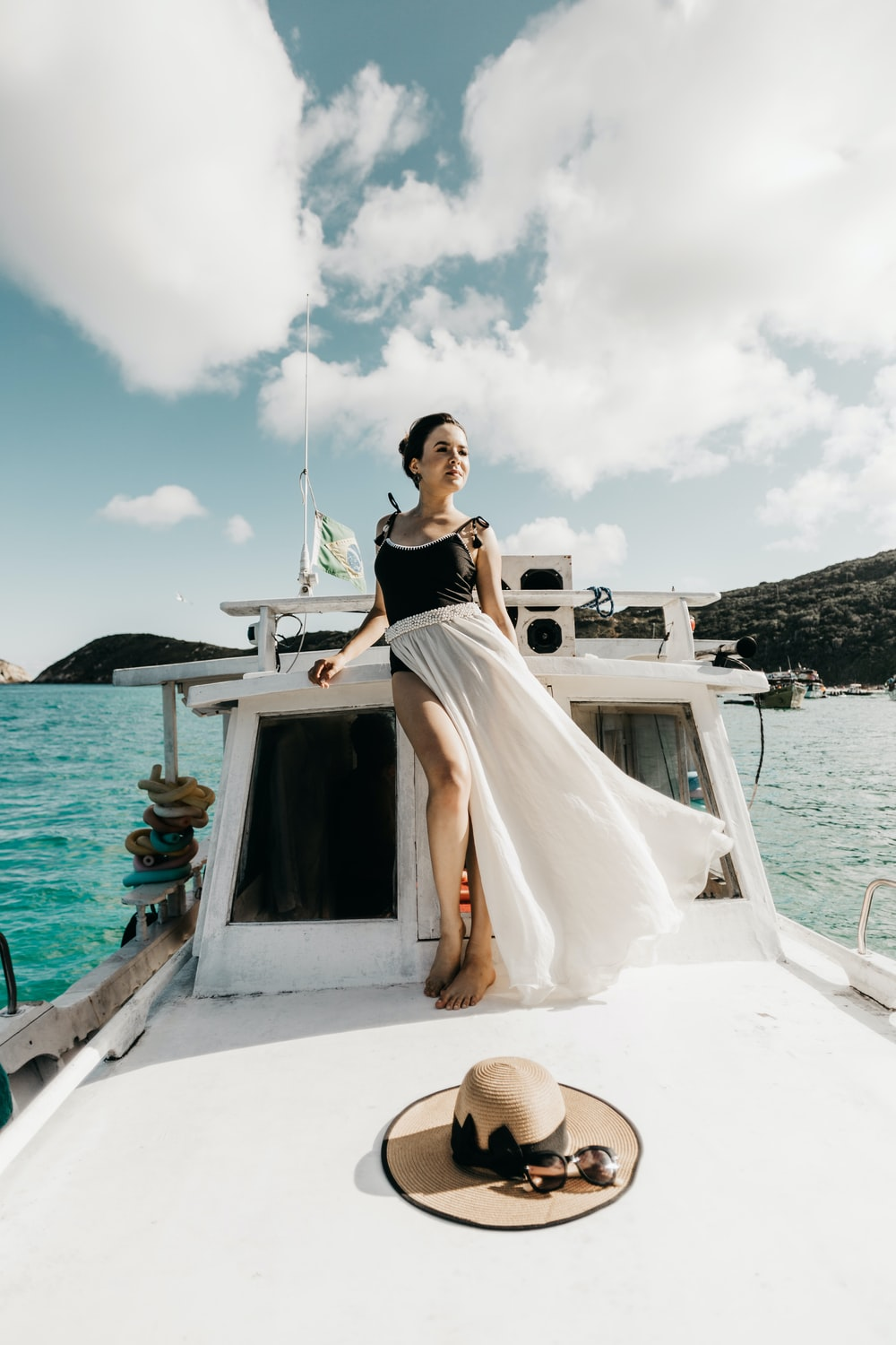 woman in white dress standing on white boat during daytime