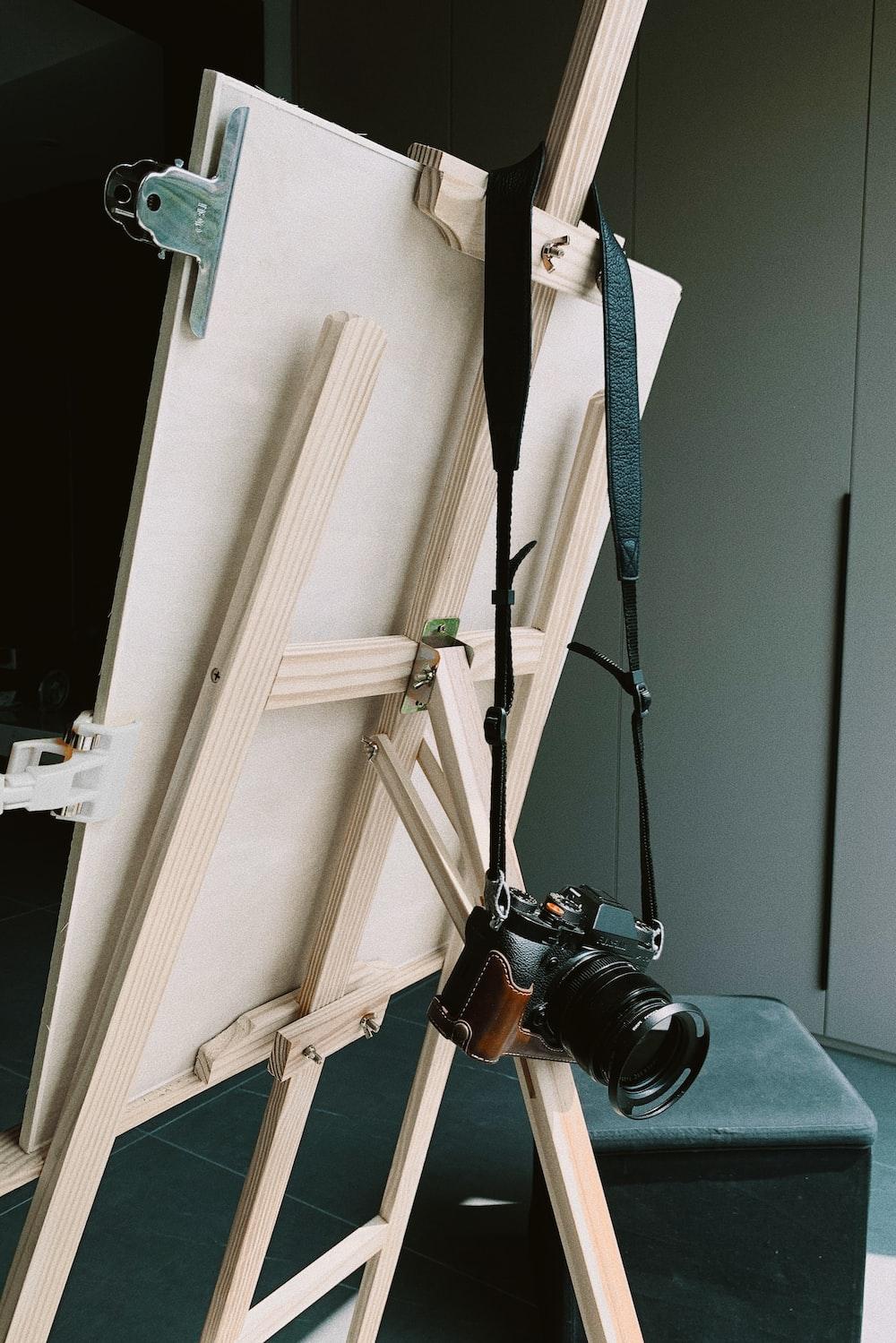 black dslr camera on white wooden cabinet