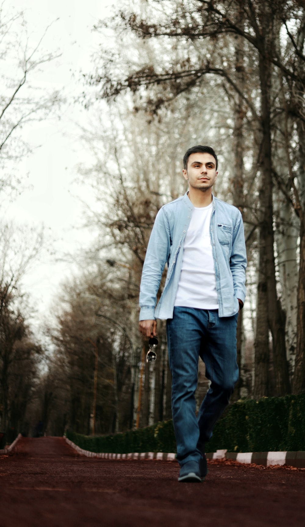 man in white dress shirt and blue denim jeans standing on green grass field during daytime