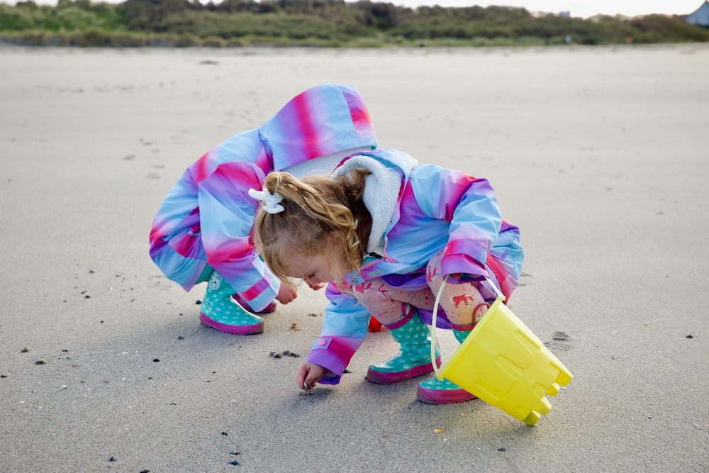 girl in pink jacket holding yellow plastic bucket on beach during daytime