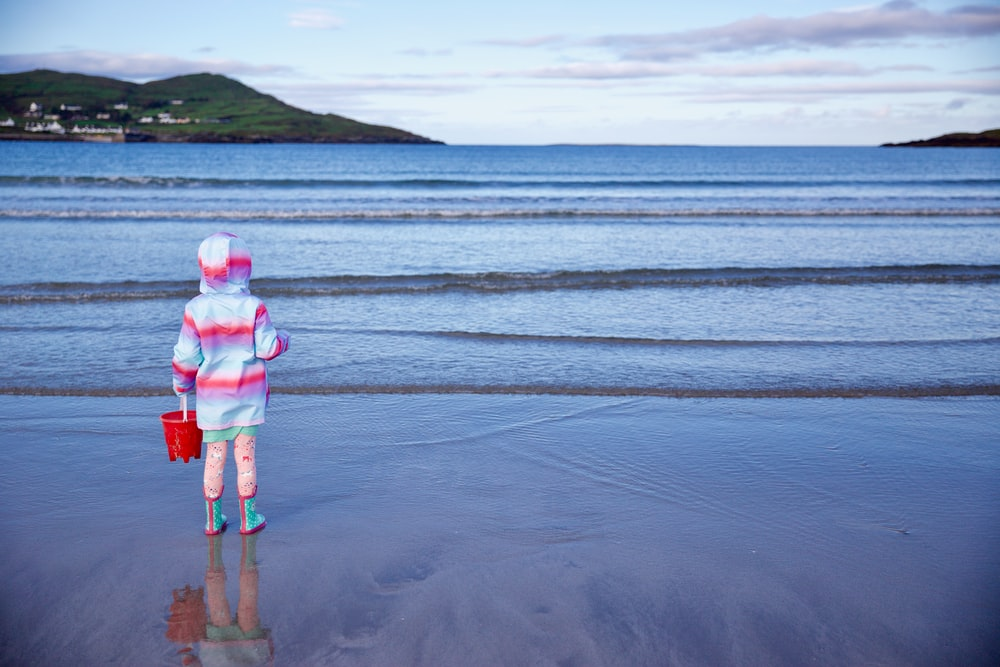 girl in pink jacket and blue denim shorts standing on beach during daytime