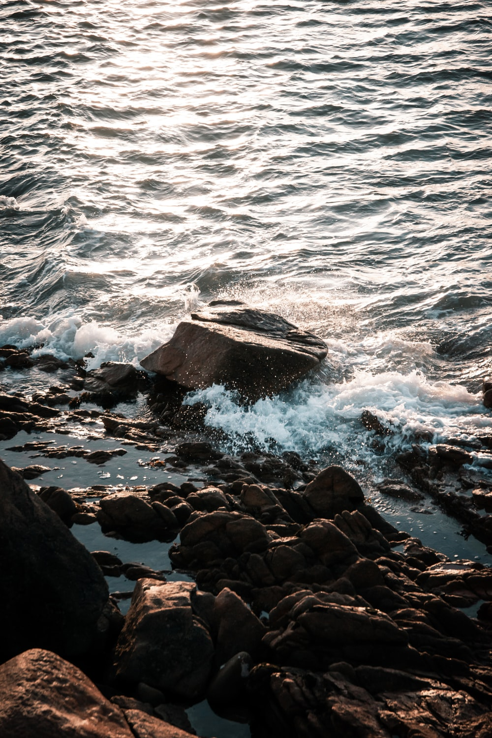 brown rocky shore with sea waves crashing on rocks during daytime