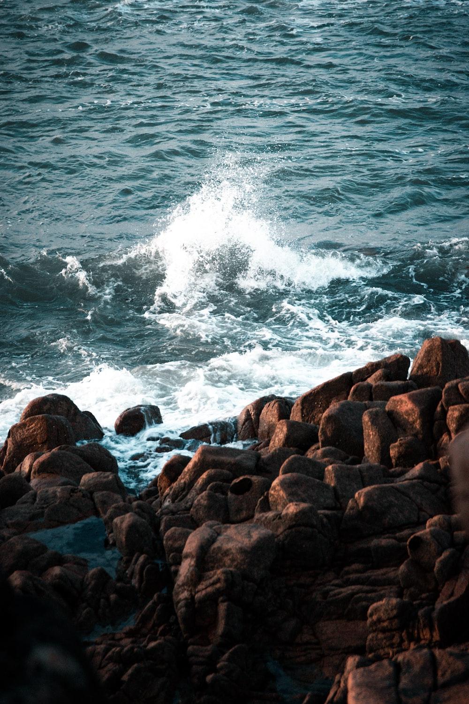 brown rocks near body of water during daytime