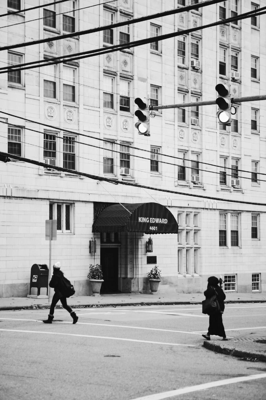 grayscale photo of man walking on sidewalk near building